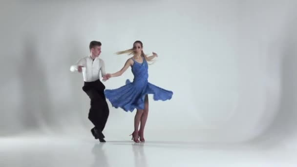 Couple is dancing salsa on white background, shadow. Slow motion