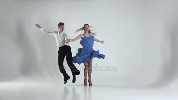 Dva mistři tančí na bílém pozadí, stín. Zpomalený pohyb