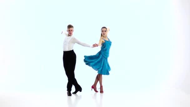 Dvojice profesionálních tanečníků provést samba, bílé pozadí. Zpomalený pohyb