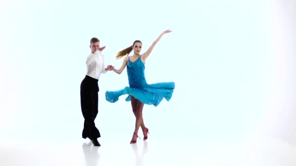 Pair of professional dancers perform rumba, white background. Slow motion