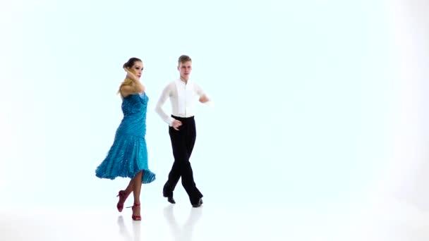 Dvojice profesionálních tanečníků provést latino, bílým pozadím. Zpomalený pohyb