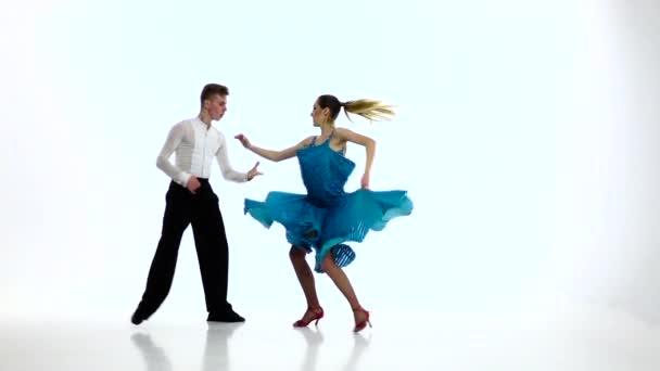 Tango dancing couple of professional elegant dancers,slow motion. White studio