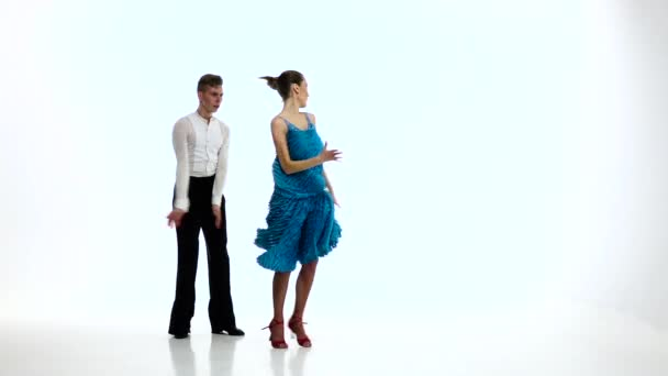 Rumba dancing couple of professional elegant dancers,slow motion. White studio