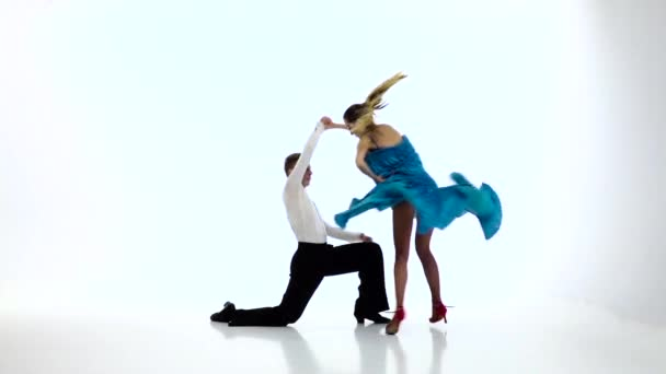 Pair graceful dancers perform jive on white background, slow motion