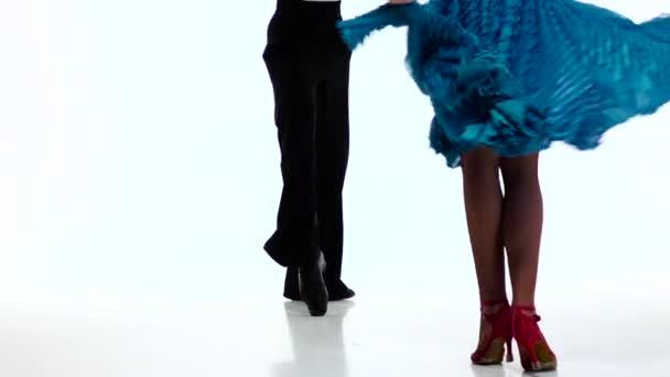 Legs pair ballroom dancers perform salsa, white background. Slow motion