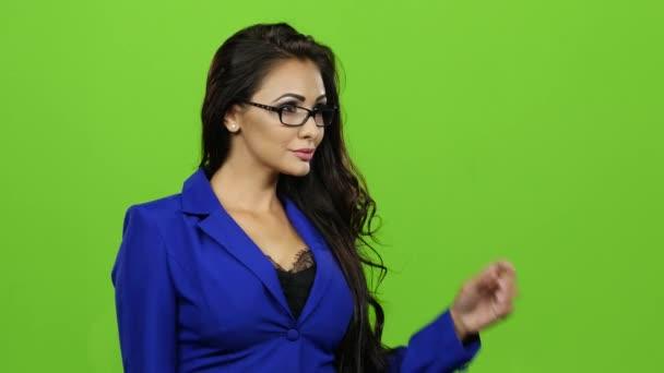 Žena v brýlích, listovala virtuální snímky. Zelené pozadí