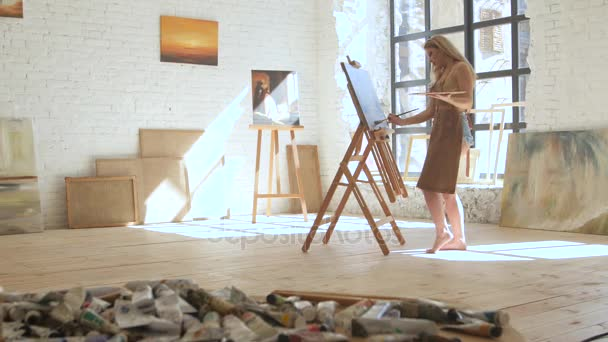Woman artist paints on canvas on easel and holds palette in art workshop