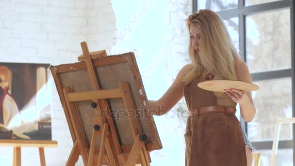 Girl artist inspired paints picture on canvas mounted on easel