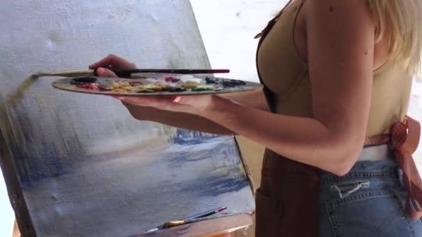Master in creazione di pittura con colori ad olio e spazzola, vista laterale