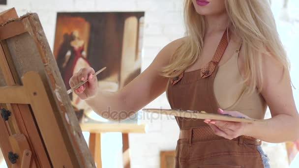 Artista dipinge il quadro su tela montata su cavalletto. Slow motion
