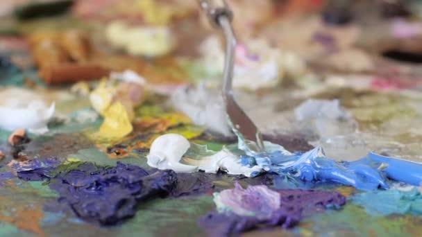 Vícebarevné olejové barvy na paletě promíchá špachtlí. Zpomalený pohyb, closeup