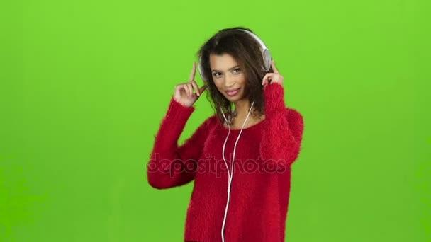 La ragazza balla e ruota con schermo di cuffie, verde. Slow motion