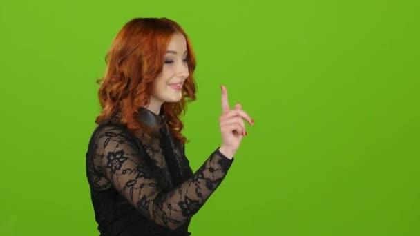 Dívka pomocí počítačové grafiky prakticky posouvá prostřednictvím fotografií. Zelená obrazovka