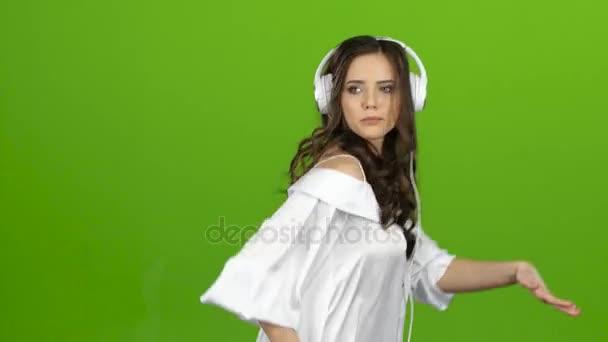 Dívka poslouchá přes sluchátka hudbu a vír kolem ní. Zelená obrazovka