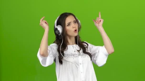 Bruna in ascolto attraverso le cuffie con musica energica e costruisce smorfie. Schermo verde
