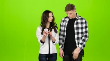 Loving guy and girl look in the phone and choose common pictures. Green screen