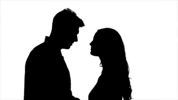 Liebendes Paar schaut einander an und beginnt sich zu küssen. Silhouette. weißer Hintergrund. Zeitlupe