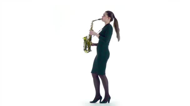 Žena hraje na saxofon jazzové melodie. Zpomalený pohyb, bílý studio