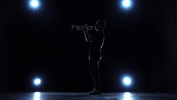 Hudebník v studio s reflektory hraje jazz trubku. Zpomalený pohyb