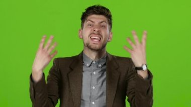 Guy gets angry, screams and curses. Green screen. Slow motion