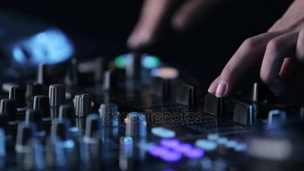 Žena Dj hrát elektronické hudby na mixážní pult v nočním klubu