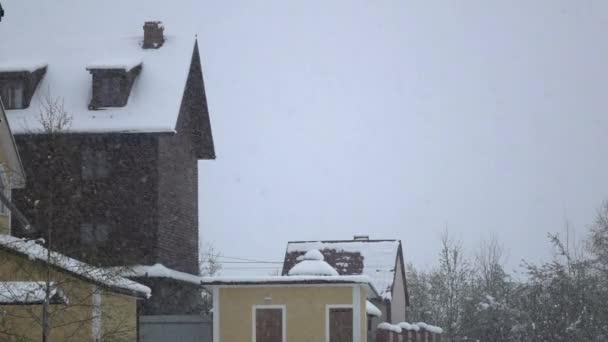 Blizzard vrhne na střechy domu bílé a čistého sněhu