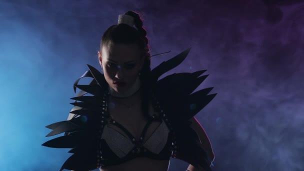 Sexy tanečnice v erotické kostýmy pózuje na kameře. Kouřové pozadí