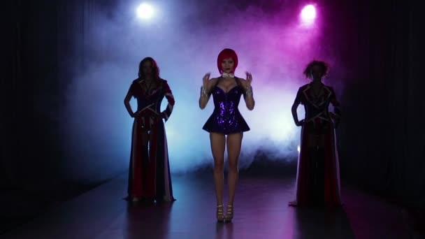 Sexy holky tanec v malém nočním klubu. Zakouřený vícebarevné pozadí