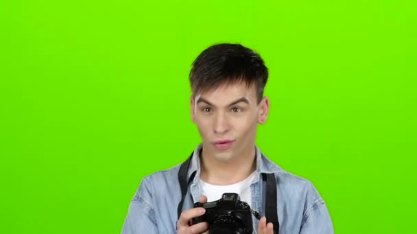 Man takes pictures of the landscapes on the professional camera. Green screen. Slow motion