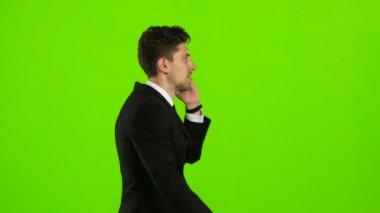 Az ember megy dolgozni, és beszél a telefonon. Zöld képernyő. Oldalnézet