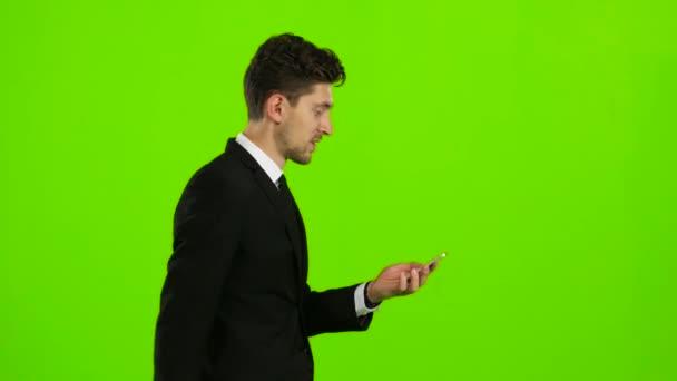 Mann schaut auf das Foto auf das Telefon und findet eine Liste der Bilder. Green-Screen. Seitenansicht