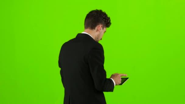 Mann schaut auf das Foto auf das Telefon und findet eine Liste der Bilder. Green-Screen. Ansicht von hinten
