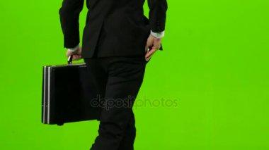 Üzletember van egy diplomata a kezét, a telefon cseng, és kezd-hoz fuss. Zöld képernyő. Hátulnézet