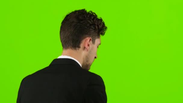 Mann zur Arbeit geht und spricht am Telefon. Green-Screen. Ansicht von hinten