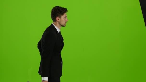 Mann zur Arbeit geht und spricht am Telefon. Green-Screen. Seitenansicht