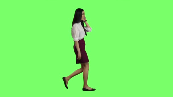 Mädchen von asiatischen Aussehen geht an ihr Telefon klingelt und sie beginnt zu reden. Green-Screen. Seitenansicht. Slow-motion