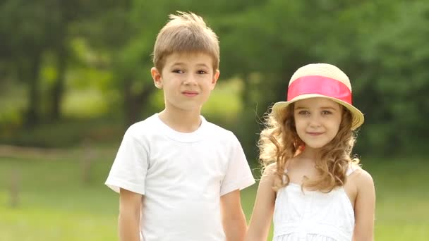 Děti v parku se drží za ruce a při pohledu do dálky. Zpomalený pohyb