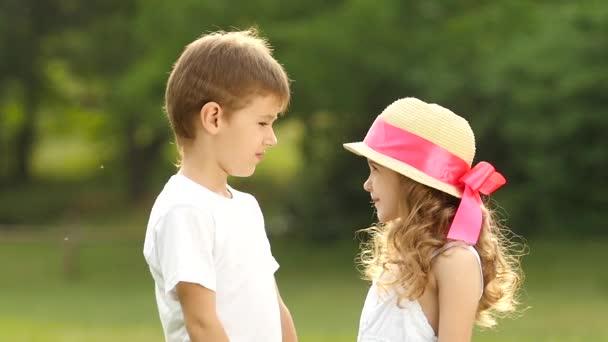 Kinder halten sich an den Händen, das Mädchen ist peinlich berührt und lächelt. Zeitlupe