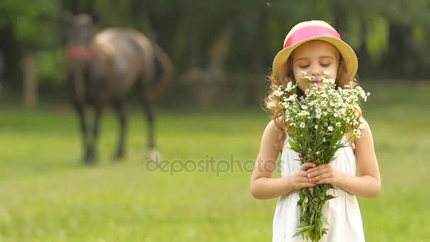 Malá holčička s divokými květy v jejich rukou sniffs je. Zpomalený pohyb