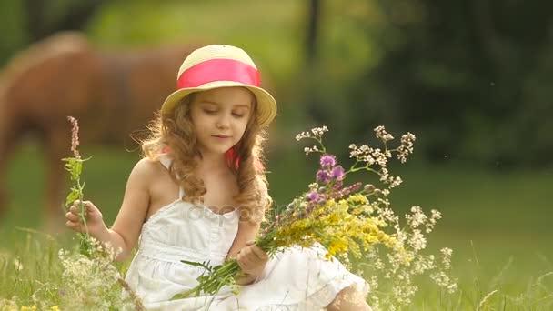 Dítě sedí na mýtině v Sarafán a klobouk, drží divokých květin a úsměvy. Zpomalený pohyb