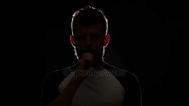 Ember egy elektronikus cigaretta tart a kezében, belélegzi, és sok füst exhales. Fekete háttér