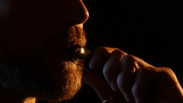 Chico exhala humo en un cuarto oscuro. Fondo negro. Cierre para ...