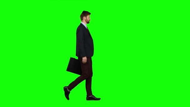 Üzletember a diplomata, a telefon cseng, és vele beszél. Zöld képernyő