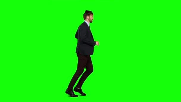 Uomo daffari correre al lavoro, è tardi per una riunione importante. Schermo verde