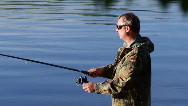 Rybář má rybářský prut v ruce a úlovky ryb pro návnady