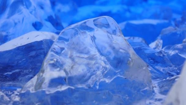 Kousky ledu leží na stole, modré osvětlení krásně leží nad fragmenty. Detailní záběr