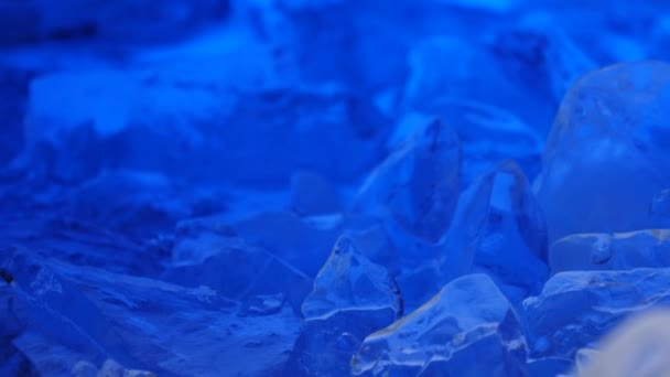 Eisstücke liegen auf dem Tisch, blaue Illumination liegt wunderschön über Fragmenten. Nahaufnahme