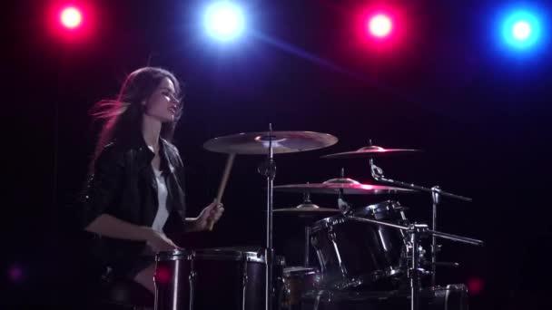 Dívka hraje na bicí. Černé pozadí. Červené modré světlo zezadu. Boční pohled. Zpomalený pohyb