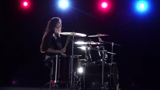Bubeník dívka s hůlkami bije rytmické hudby. Černé pozadí. Červené světlo modré. Boční pohled. Zpomalený pohyb