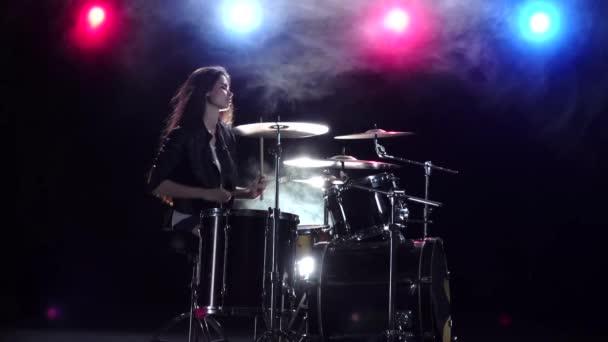 Dívka hraje na bicí a úsměvy. Na pozadí černého kouře. Červené modré světlo zezadu. Boční pohled. Zpomalený pohyb